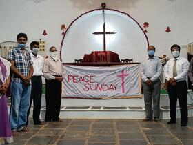 """masked congregation members stand on either side of """"Peace Sunday"""" banner draped altar"""
