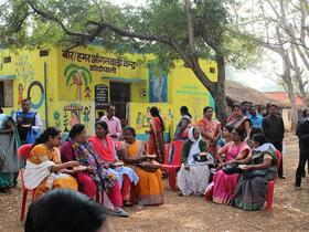 women dressed in bright colours sit outdoors sharing a meal