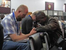a black man and a white man hold hands in prayer